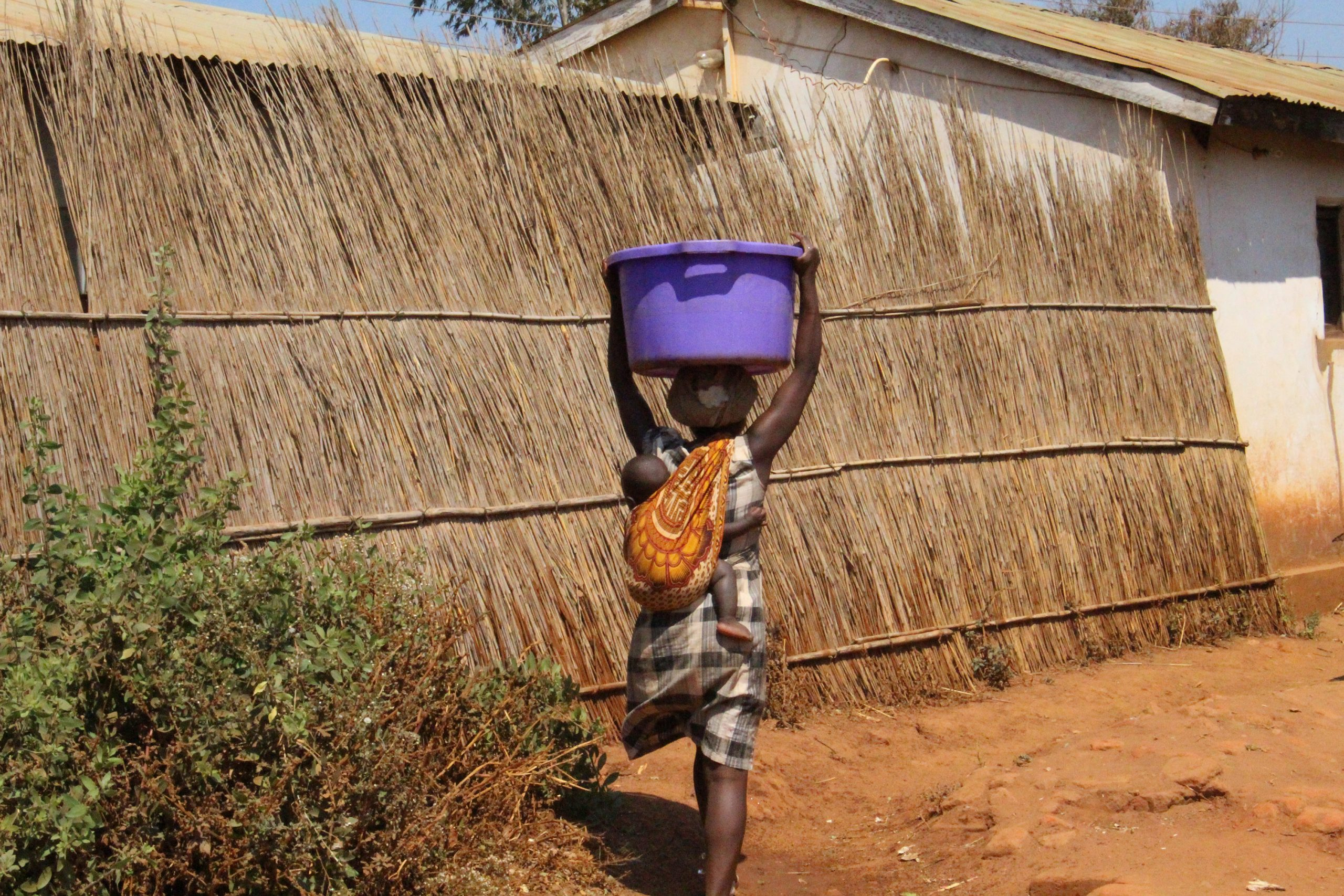 A woman in Malawi carries a 30-liter container of water on her head while also carrying an infant who is strapped to her back. Photo from Ellis Adjei Adams.